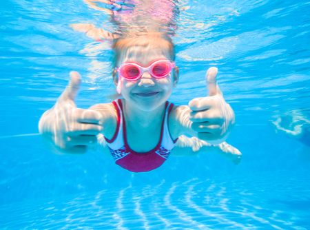 girl swimming underwater giving two thumbs up