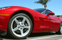 Closeup of a red two-door sports car with a blue sky and palm tree in the background
