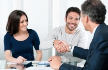 A couple sits across from a real estate agent, the husband is shaking the agent's hand